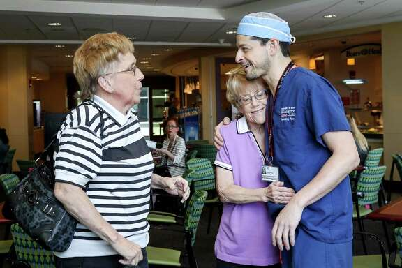 Marian Fields, center, hugs Dr. Jesse Selber, assistant professor of plastic surgery at M.D. Anderson, as her sister Mary Jane Fields talks to Dr. Selber, Friday, July 28, 2017, in Houston. Dr. Selber and his team harvested skin and tissue from Mary Jane and grafted it onto the back of Marian to help treat a rare and lethal form of skin cancer.