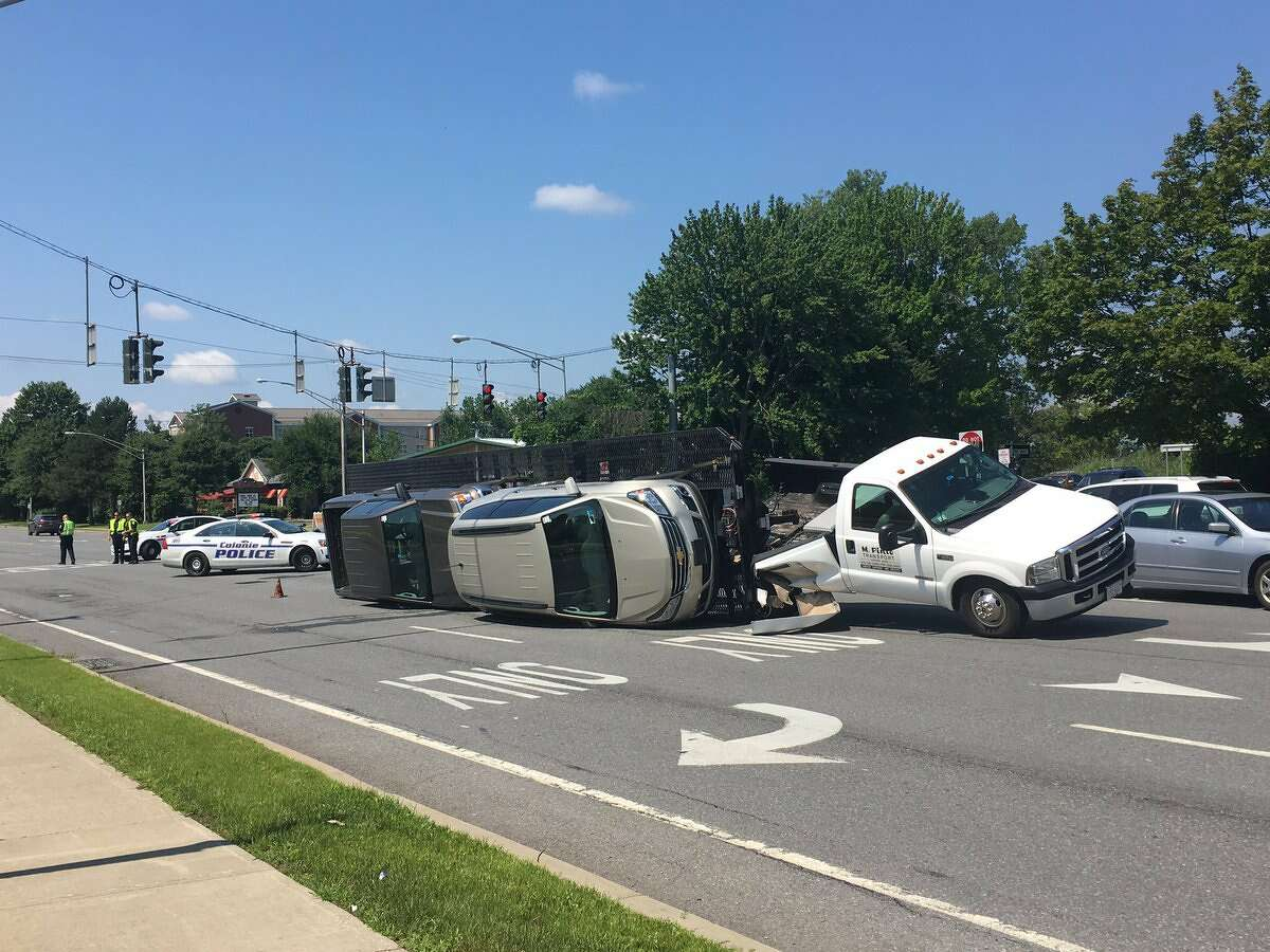 A flatbed trailer loaded with a sport utility vehicle and a pickup truck flipped Tuesday, Aug. 1, 2017, as the truck pulling it exited the Northway onto Wolf Road in Colonie, N.Y. No one was injured but police warned drivers to expect delays.