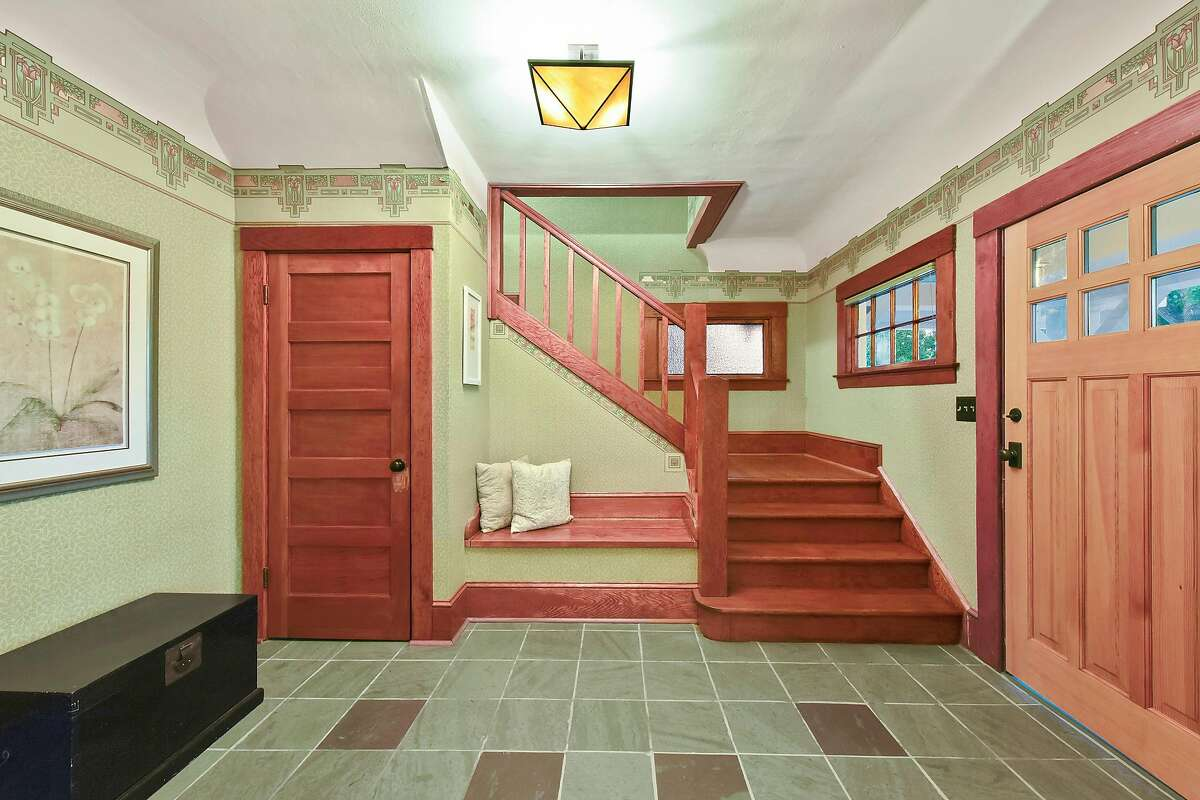 The home opens to a tiled foyer with a sitting bench.