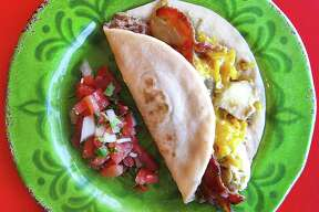 Trash Can Taco with eggs, bacon, potatoes, beans and cheese on a handmade flour tortilla from Pepe's Tacos N Salsa.