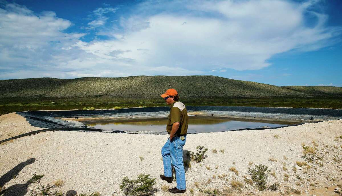 Ranch manager Will Hughes looks over a retention pond filled with water from a well on the Apache Ranch in Van Horn last month.