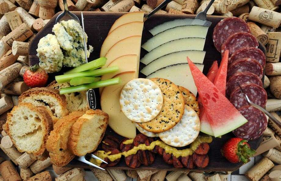 Cave a Vin, New Haven: A cheese board with blue Stilton, Manchego, smoked Gouda, soprasatta, linguica (all hand-cut), chef Jamie Trumbull's homemade brown mustard, Jude's bread and fresh fruit. Mara Lavitt/Register