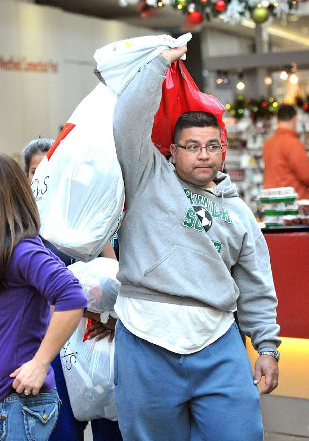 John Arteaga of Bridgeport weaves his way through the crowds at the Westfield Milford Post Mall as he does his holiday shopping. Peter Casolino/New Haven Register