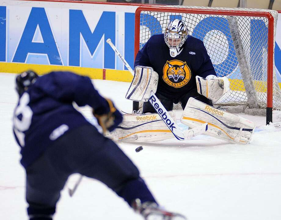 """Pittsburg, PA--  Quinnipiac goalie Eric Hartzell blocks a shot during a practice at the Consol Energy Center in Pittsburg, PA as they prepare for the Frozen Four finals.  Photo-Peter Casolino/Register <a href=""""mailto:pcasolino@newhavenregister.com"""">pcasolino@newhavenregister.com</a>"""
