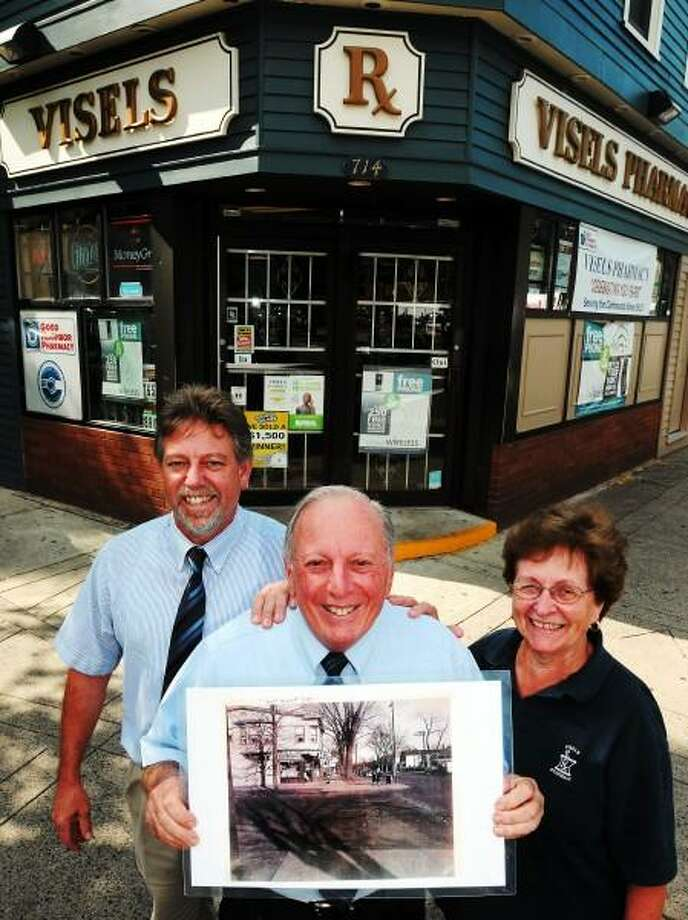 August 6, 2013. The Funaro family is celebrating 100 years of Visels Pharmacy in New Haven. Edmund Jr. left, Edmund Sr., center, with photo of Visels from 1949, and Janet Funaro. Mara Lavitt/New Haven Register