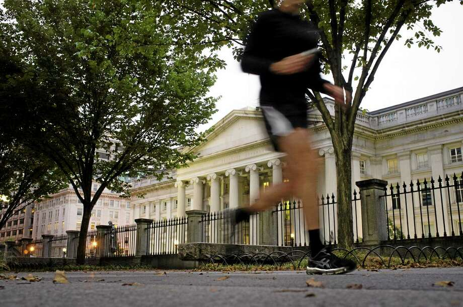 A jogger on an early morning run passes the U.S Treasury Building in Washington, Wednesday, Oct. 16, 2013, a day before the stalemate in Congress over the budget could cause the government to reach its borrowing limit.  (AP Photo/J. David Ake) Photo: AP / AP