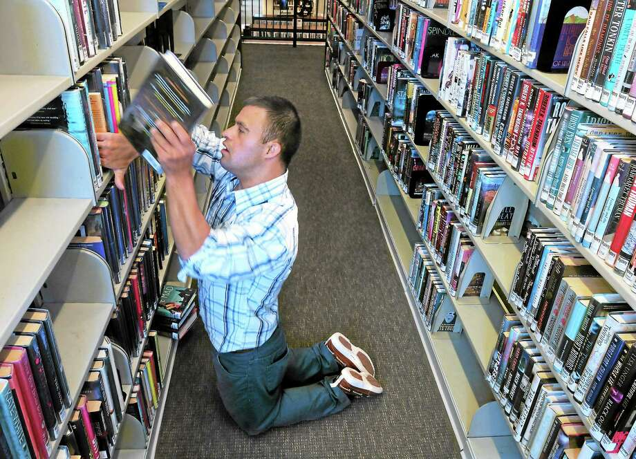 Patrick Jordan of West Hartford was part of a landmark Connecticut case that established a state mandate to mainstream special needs children in schools. One of his jobs is to shelve books at the West Hartford Public Library two days a week, a job recommended to him while he was at Manchester Community College. Photo: Mara Lavitt — New Haven Register      / Mara Lavitt