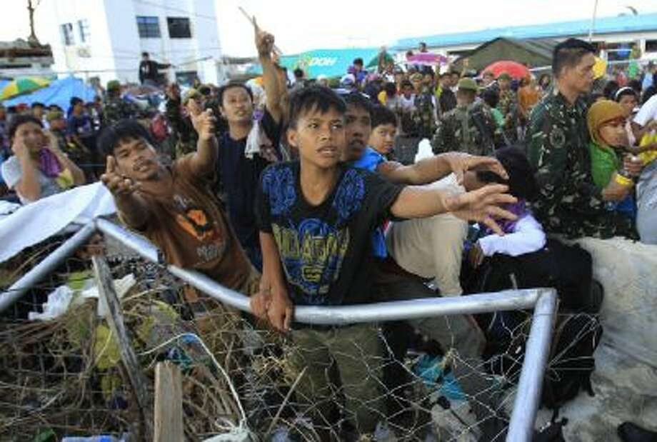 Survivors of Typhoon Haiyan plead with military for water as they wait in the sun on the airstrip for an evacuation flight in Tacloban, central Philippines, Thursday.