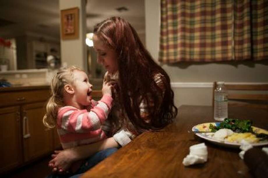 Maggie Barcellano sits down for dinner with her daughter, Zoe, 3, at Barcellano's father's house in Austin, Texas, who lives with her father, enrolled in the food stamps program to help save up for paramedic training while she works as a home health aide and raises her daughter.