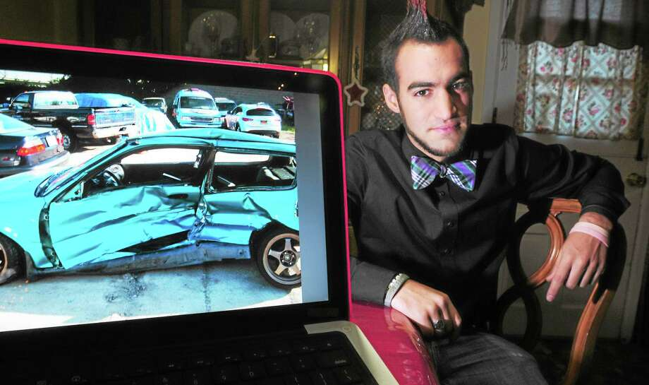 Vincent Ramaglia at his home in Trumbull by a photograph of the crumpled remains of a 1992 Honda Civic he was driving on June 1, 2011, when a drunken driver hit him. Photo: Arnold Gold — New Haven Register