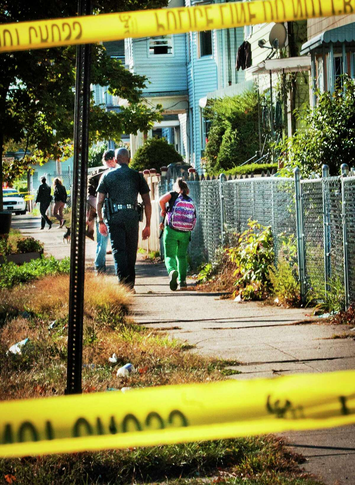 A police officer escorts a student home from school down Lombard Street in New Haven in October 2013. Police roped off the area due to a shooting.