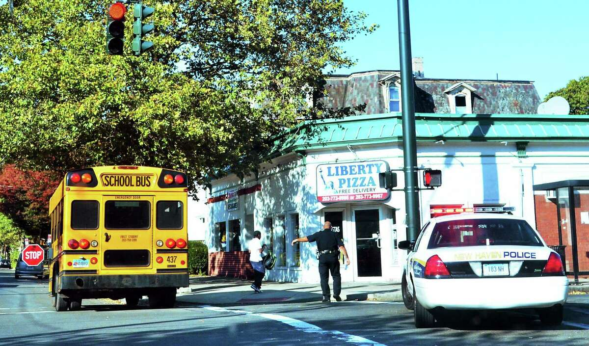 Melanie Stengel — New Haven Register A school bus stops at the corner of Ferry and Lombard streets where police investigate a shooting in October 2013.