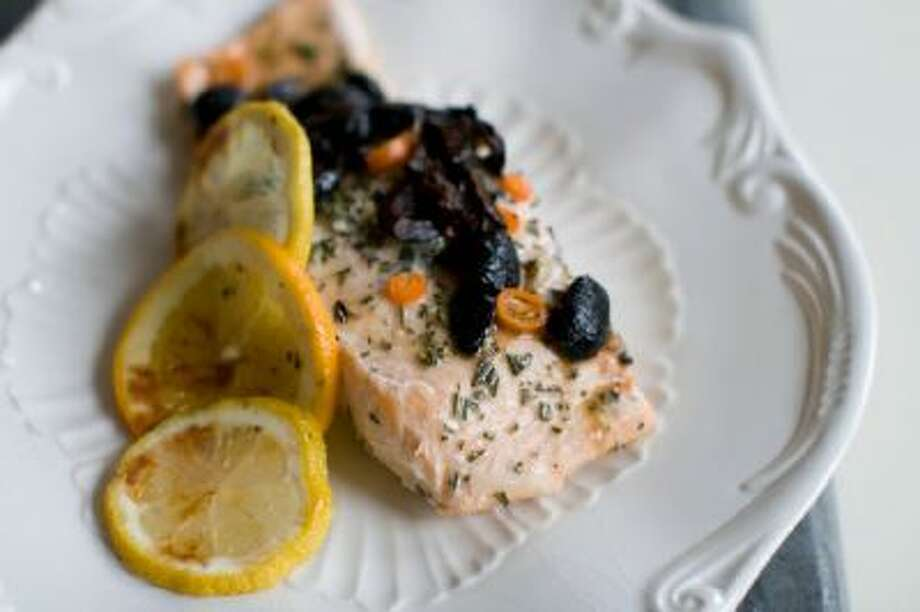 Salmon that has been baked in a bag with citrus, olive and chilies in Concord, N.H. The bag keeps the flavor and moisture trapped inside during cooking, allowing the juices from the fish and the other ingredients to mingle and become a wonderful sauce.