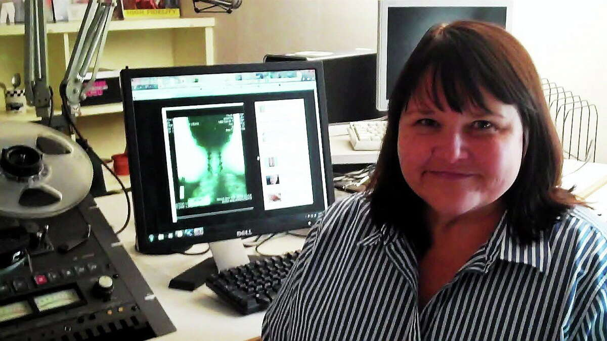Shelley Merrill of Norwich poses next to an X-ray of her neck, showing some of the injuries she suffered after a drunk driver crashed into the vehicle in which she was a passenger in 2007.