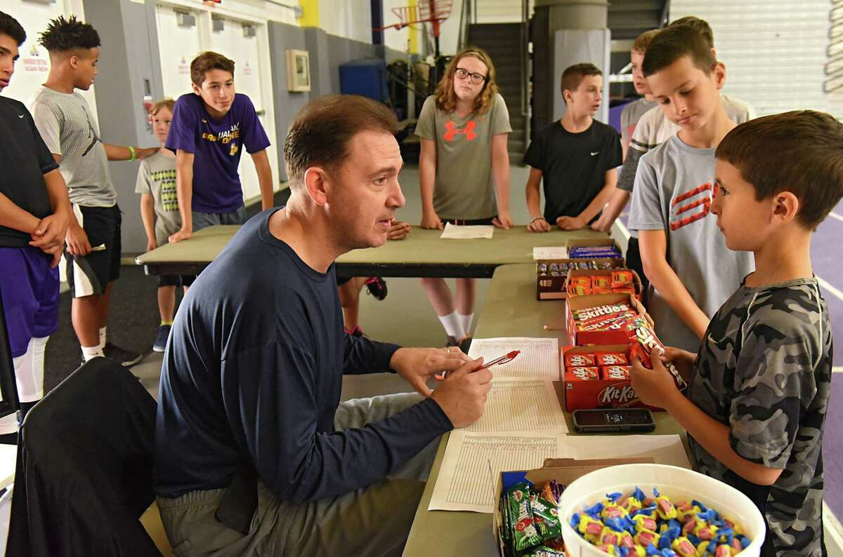 UAlbany coach Will Brown sells Skittles to Joshua Melchier, 8, of Albany, right, as he works at the snack table during the Will Brown basketball camp at SEFCU Arena at University at Albany on Tues. Aug. 1, 2017 in Albany, N.Y. (Lori Van Buren / Times Union)