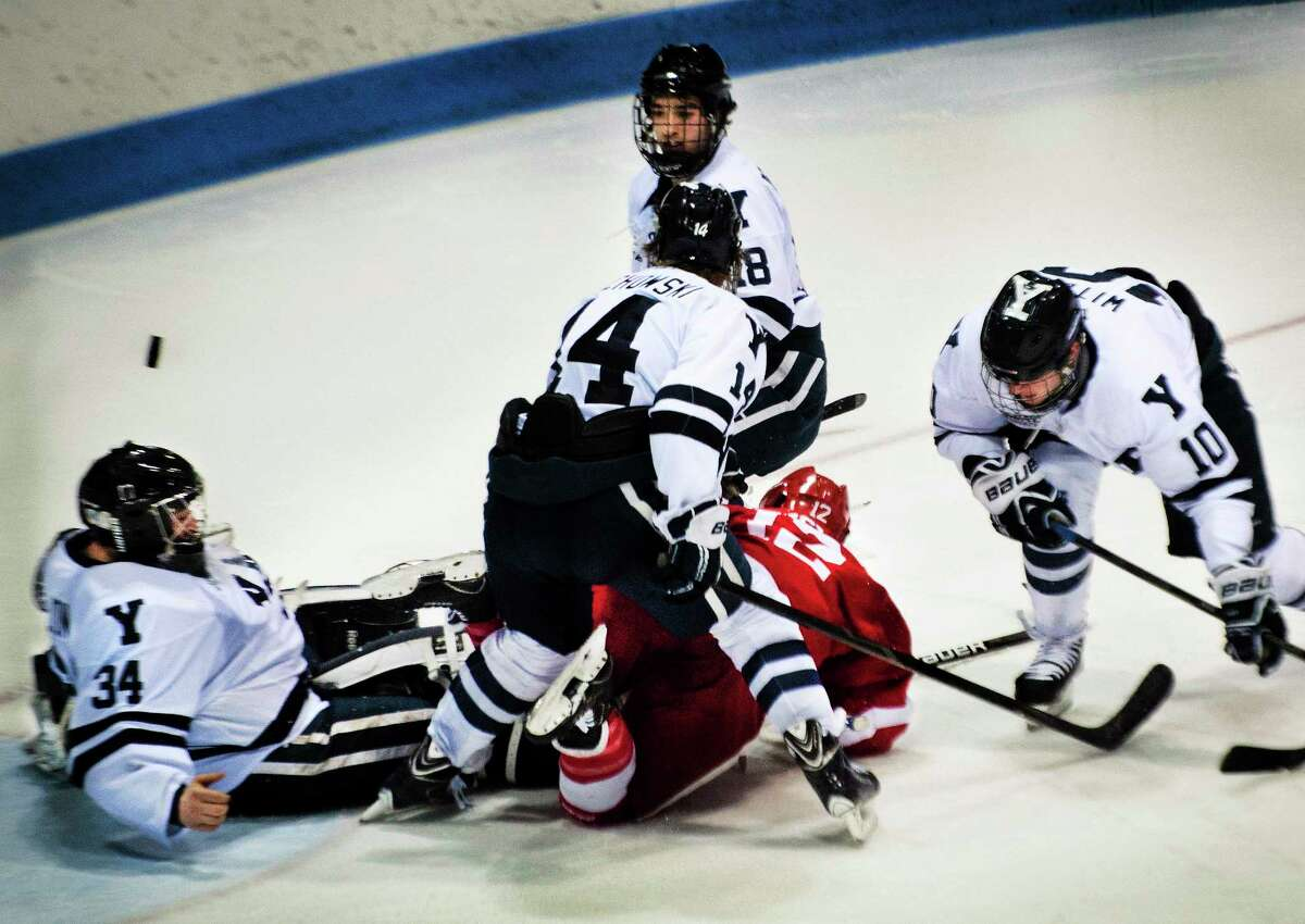 Melanie Stengel — New Haven Register Yale goalie, Alex Lyon, is surrounded by teammates Kenny Agostino, Ry Obuchowski, Mitch Witek, and Cornell's John Knisley, in 2nd period action.