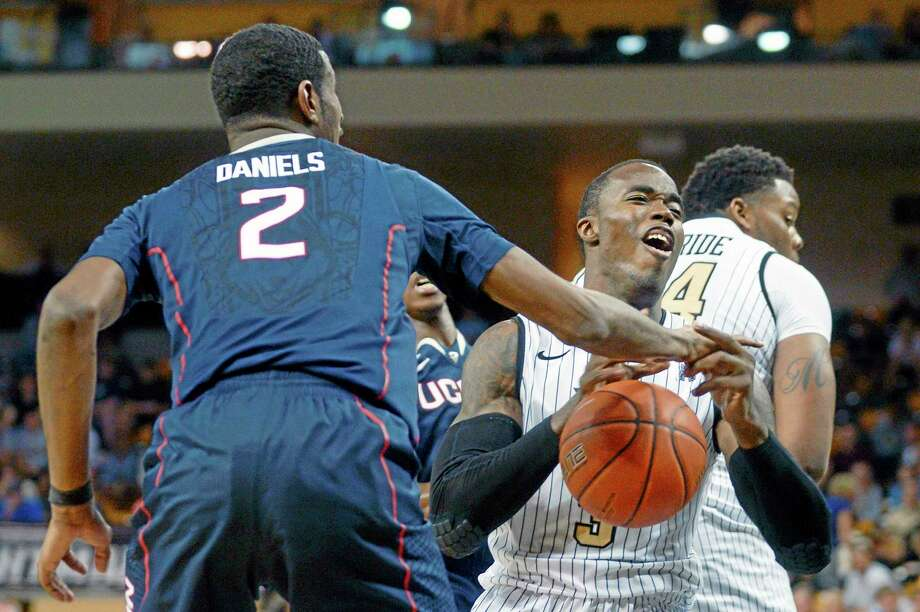 Central Florida guard Isaiah Sykes, right, is fouled by Connecticut forward DeAndre Daniels (2), while driving to the basket, during the second half of an NCAA college basketball game in Orlando, Fla., Sunday, Feb. 9, 2014. Connecticut won 75-55. (AP Photo/Phelan M. Ebenhack) Photo: AP / FR121174 AP