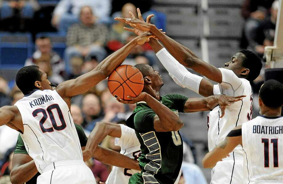 Connecticut's Lasan Kromah, left, and Amida Brimah, right, block a shot-attempt by South Florida's Martino Brock, center, during the first half of an NCAA college basketball game on Wednesday, Feb. 12, 2014, in Hartford, Conn. (AP Photo/Jessica Hill) Photo: AP / FR125654 AP