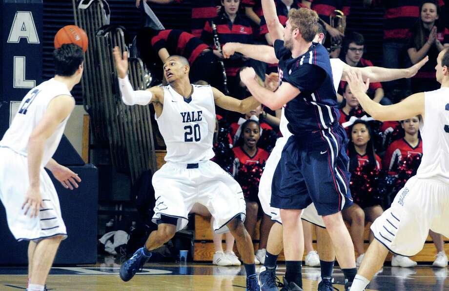 Yale's Javier Duren reaches for the ball against Penn in Friday's game in New Haven. Yale won 69-54 for its fifth straight victory. Photo: Arnold Gold — Register
