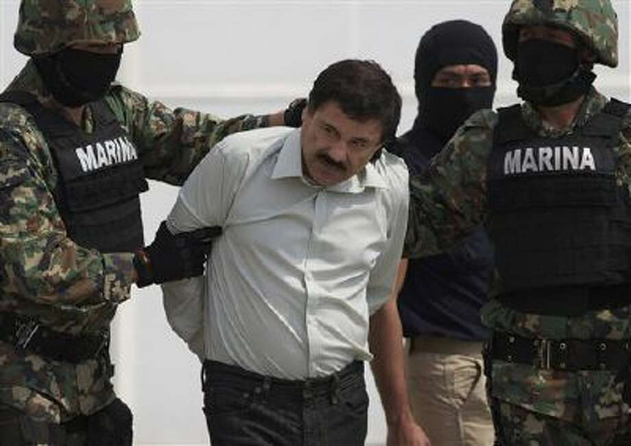 """In this Saturday, Feb. 22, 2014 photo, Joaquin """"El Chapo"""" Guzman is escorted to a helicopter in handcuffs by Mexican navy marines at a navy hanger in Mexico City, Mexico. Guzman, the head of Mexico's Sinaloa Cartel, was captured overnight in the beach resort town of Mazatlan. (AP Photo/Eduardo Verdugo) Photo: AP / AP"""