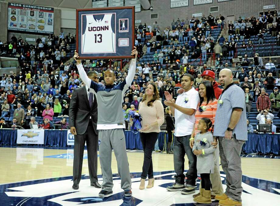 Shabazz Napier, joined by his family on Senior Night, holds up a plaque before No. 19 UConn's 69-63 win over Rutgers at Gampel Pavilion in Storrs on Wednesday. Photo: Fred Beckham — The Associated Press   / FR153656 AP