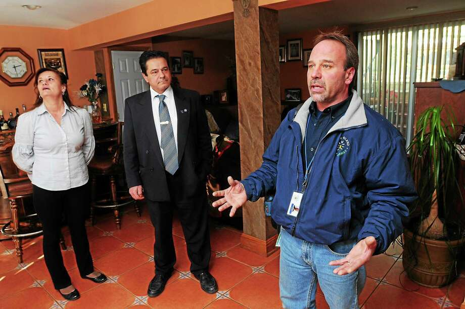 Tom Prizio, right, of New England Smart Energy explains to Ansonia  Mayor David Cassetti and his wife, Alfonsina, about the home energy  audit process at their home Thursday. Photo: Journal Register Co.