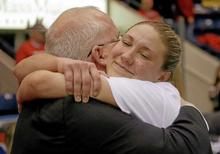 Marist guard Casey Dulin of Milford hugs her head coach, Brian Giorgis, before the trophy presentation ceremony after the Red Foxes beat Quinnipiac 70-66 in the Metro Atlantic Athletic Conference tournament championship in Springfield, Mass., on Monday. Photo: Stephan Savoia — The Associated Press   / AP