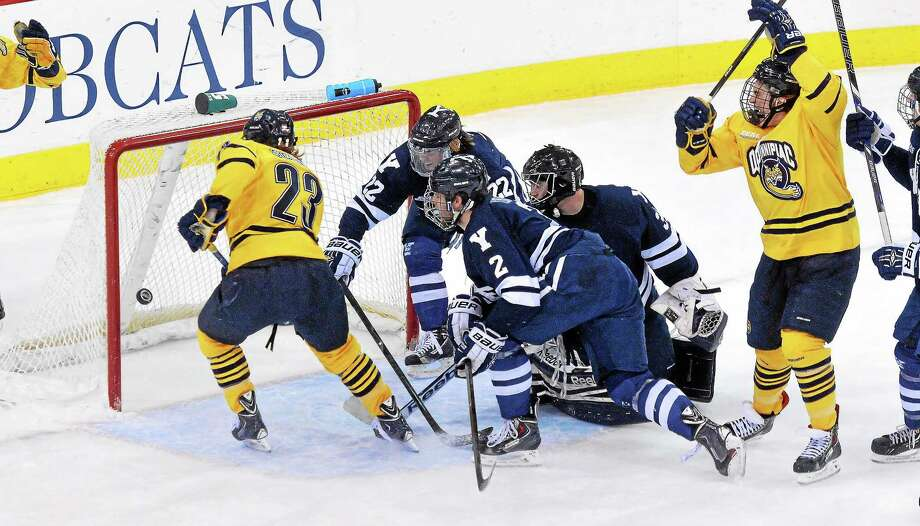 Quinnipiac's Tommy Schutt puts the puck past Yale goalie Alex Lyon and defenders Tommy Fallen, rear, and Gus Young in the first period of the Bobcats' 5-3 win on Saturday night in Hamden. Photo: Peter Casolino — Register
