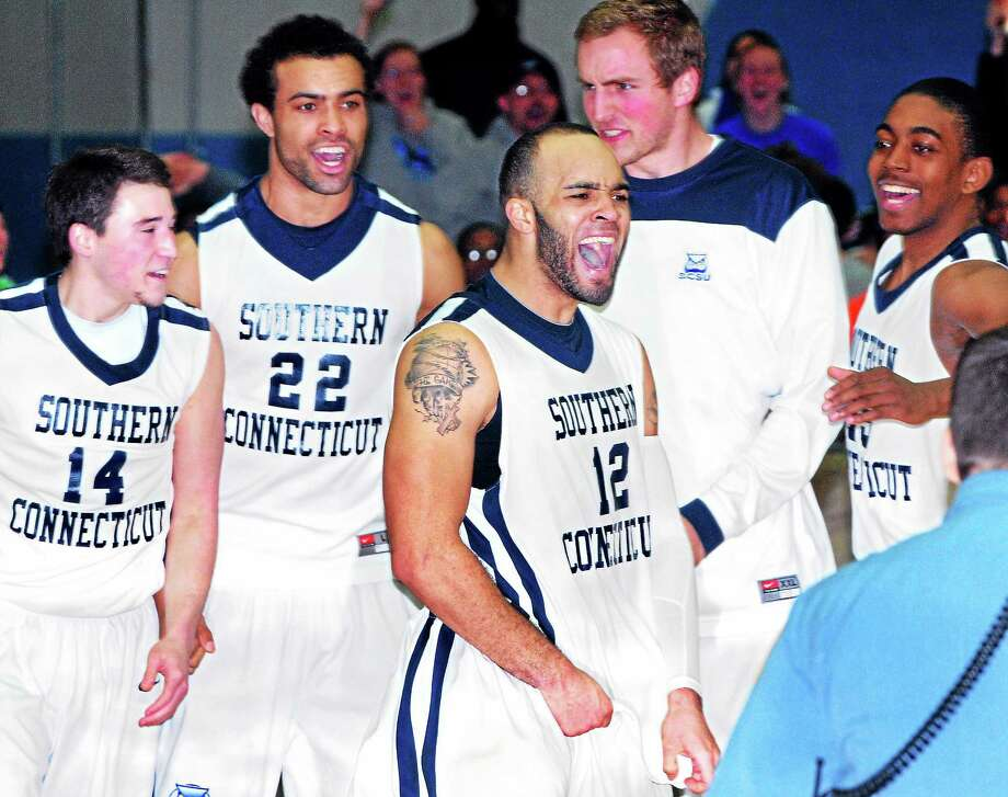 SCSU's Tylon Smith, center, celebrates with his team after scoring in the final seconds to beat Franklin Pierce 79-77 on Sunday. Photo: Arnold Gold — Register