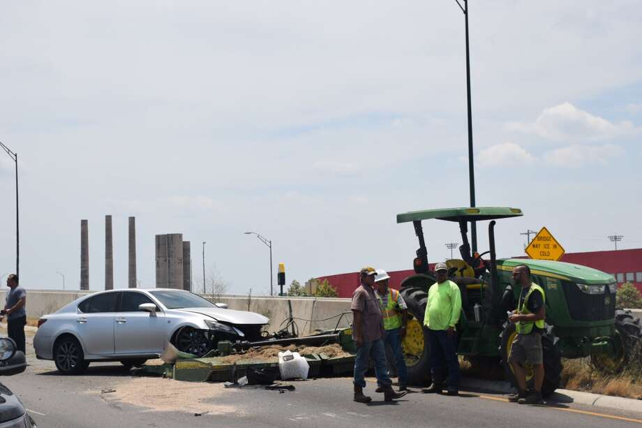 The eastbound lanes of Wurzbach Parkway were closed Tuesday after a crash involving three vehicles and two John Deere tractors. Photo: Caleb Downs / San Antonio Express-News
