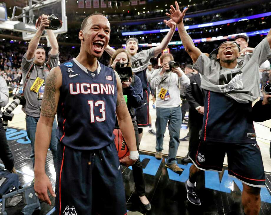 Connecticut's Shabazz Napier (13) celebrates after his team defeated Michigan State 60-54 in a regional final at the NCAA college basketball tournament, Sunday, March 30, 2014, in New York. Napier scored 17 points of his 25 points in the second half. (AP Photo/Frank Franklin II) Photo: AP / AP