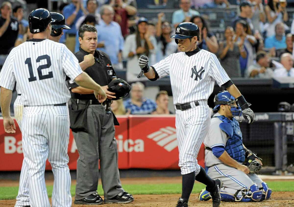 The Yankees' Ichiro Suzuki, right, is greeted by Chase Headley (12) and Brian McCann after hitting a three-run home run in Friday's 6-4 win over the Blue Jays.