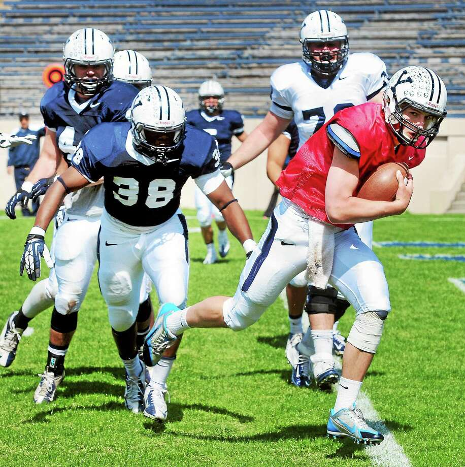 Yale quarterback Morgan Roberts (right) crosses into the endzone during the annual Blue-White scrimmage at the Yale Bowl on 4/19/2014. Photo: (Arnold Gold-New Haven Register)