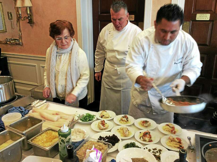 Mary Tagliatela, who with her late husband founded Saybrook Point Inn & Spa, and chef Leslie Tripp watch as sous chef Gese Rodriguez plates up baked cod. Photo: STEPHEN FRIES