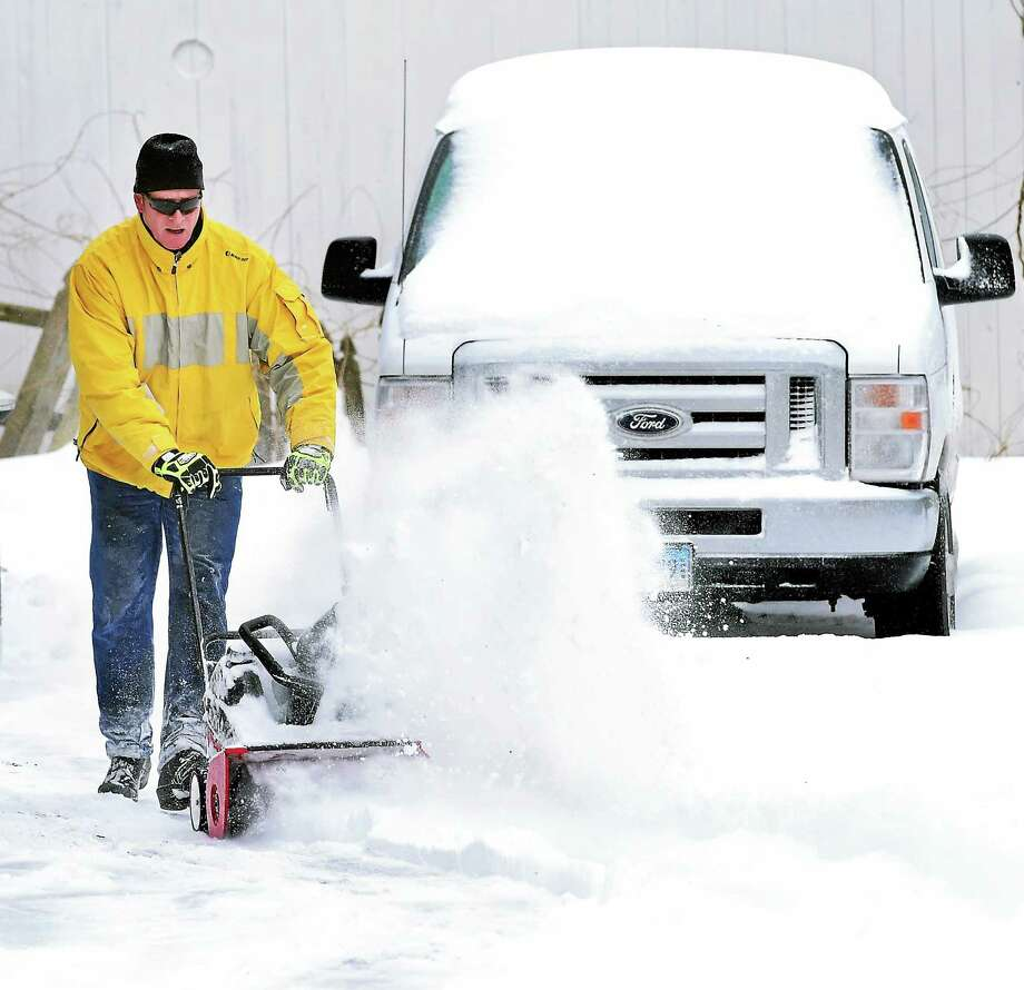 In this Feb. 2 file photo, Daniel Blanchet assists his neighbor with her driveway on Elton Street in Milford. Photo: Arnold Gold — New Haven Register