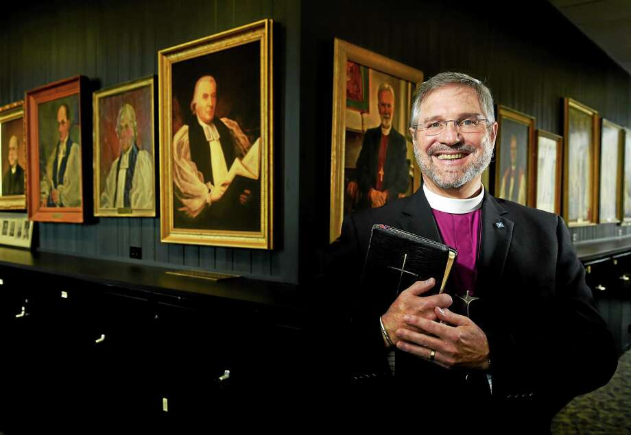 Bishop Ian Douglas, bishop of the Episcopal Diocese of Connecticut with painting of past bishops of the the Connecticut Diocese in the diocese Meriden offices. Douglas is one of four candidates to be elected presiding bishop of the Episcopal Church n the U.S. at its General Convention on June 27. Tuesday, June 16, 2015. Photo: (Peter Hvizdak - New Haven Register)   / ©2015 Peter Hvizdak