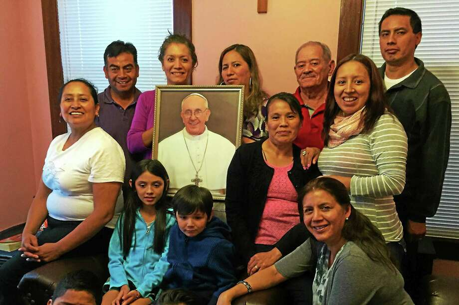Members of Fair Haven's St. Rose of Lima church pose with a portrait of Pope Francis on Tuesday, Sept. 22, in New Haven. More than 100 church members, including those pictured here, are boarding buses on Sunday to attend the pope's mass in Philadelphia. Photo: Esteban L. Hernandez — New Haven Register