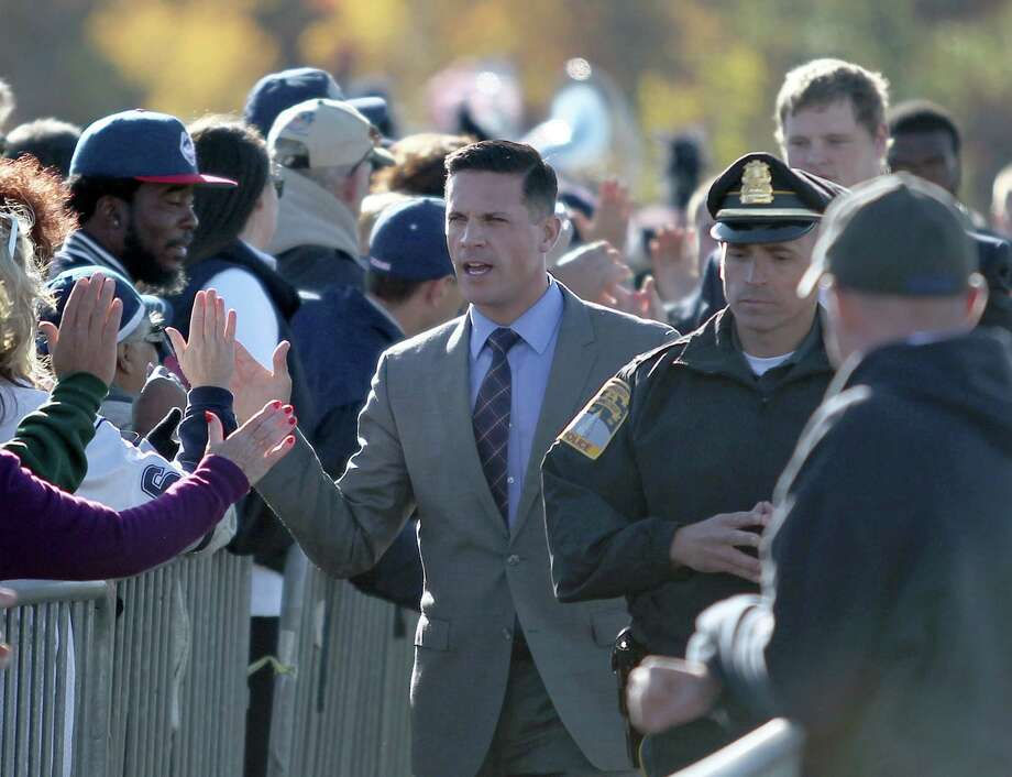 UConn coach Bob Diaco high-fives fans as he leads his team to the field before Saturday's game against South Florida in East Hartford. Photo: Mary Schwalm — The Associated Press   / FR158029 AP