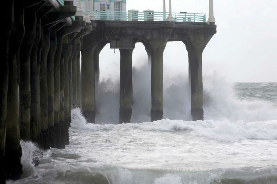The Manhattan Beach pier is hit by high waves caused by the El Nino storm in Manhattan Beach, Calif. on Jan. 6, 2016. The system Wednesday will pack colder temperatures, stronger winds and heavier rainfall than the two previous storms that have battered the state since the weekend. Photo: AP Photo/Nick Ut   / AP