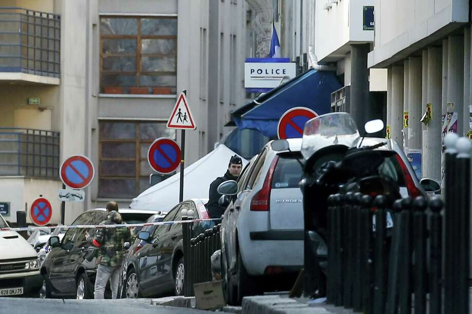A police officer guards the police station, seen in background, after officers shot and killed a knife-wielding man wearing a fake explosives vest,  in Paris, Thursday, Jan. 7, 2016. Officers shot and killed a knife-wielding man wearing a fake explosive vest at a police station in northern Paris on Thursday, French officials said, a year to the day after an attack on the French satirical newspaper Charlie Hebdo launched a bloody year in the French capital. Photo: AP Photo/Michel Euler    / AP