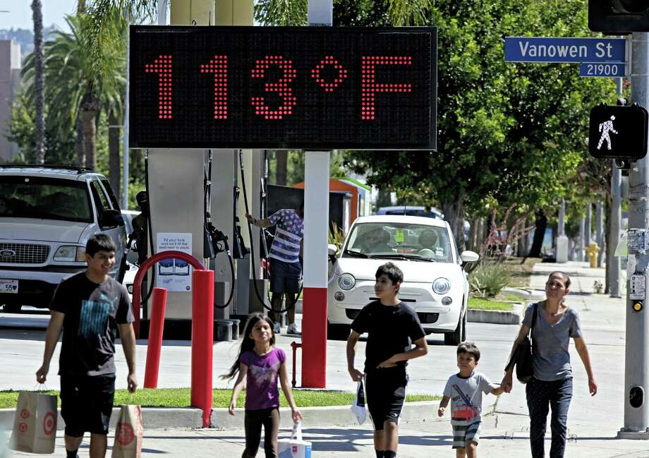 AP Photo/Richard Vogel, File  In this Aug. 15, 2015 photo, pedestrians walk past a digital thermometer reading 113 degrees Fahrenheit in the Canoga Park section of Los Angeles. Earth last year wasn't just the hottest year on record, but it left a century of temperature high marks in its hot dust. Photo: AP / AP