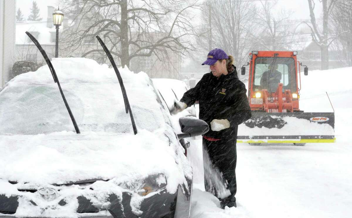 Laurie Wiles, a supervisor in dining services at Williams College in Williamstown, Mass., clears the snow off of her car on Thursday, Feb. 9, 2017., at the end of her shift during a winter storm which brought a foot of snow to the area.