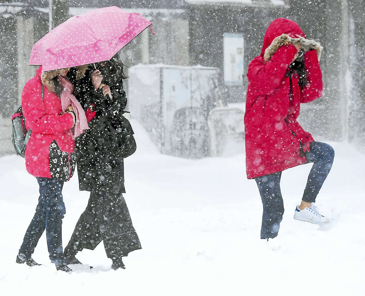 Pedestrians brave the snowstorm as they cross Chapel Street to York Street in New Haven on Thursday.