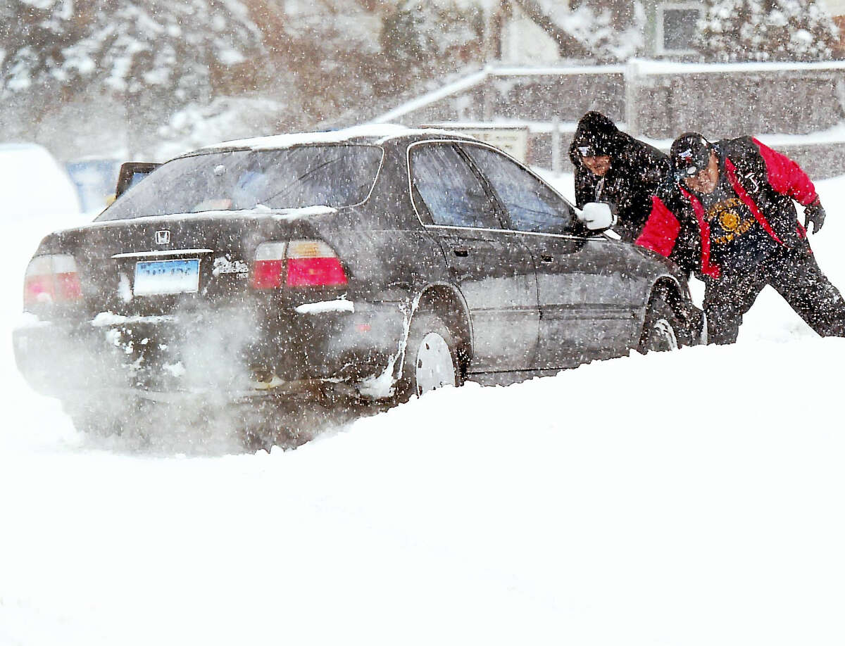 Good Samaritans help push a car stuck in the snow on Middletown Avenue in New Haven during the snowstorm on Thursday.