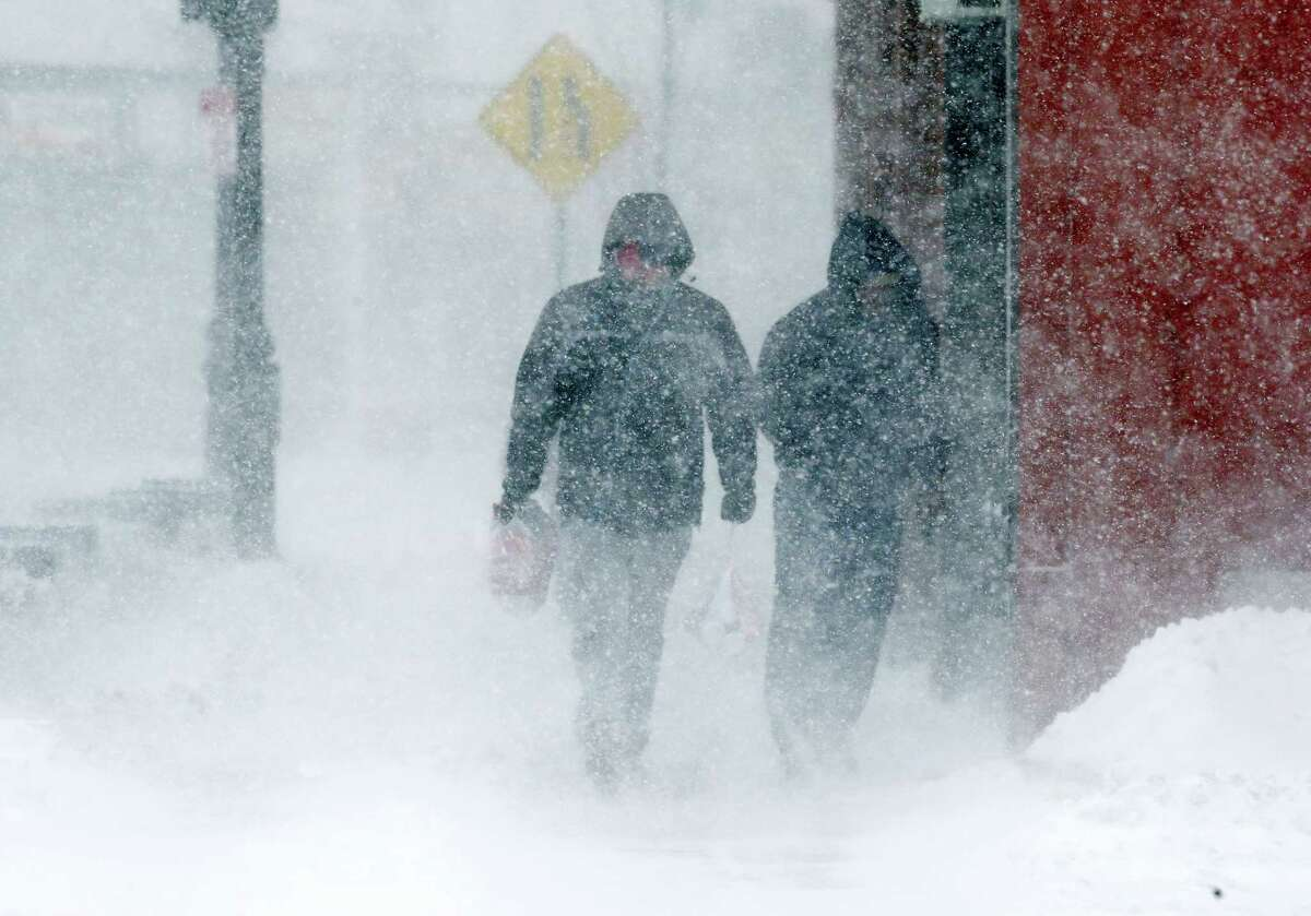 Pedestrians walk in whiteout conditions during a snowstorm Thursday in Framingham, Mass.