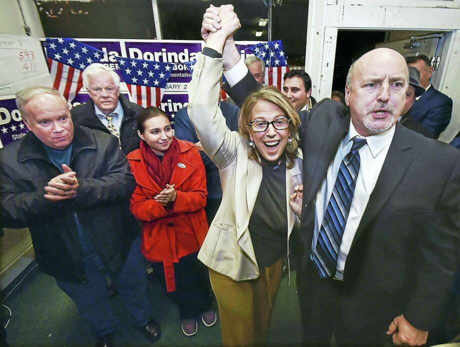 Republican Edward R. Granfield raises the hand of Democrat Dorinda Keenan Borer at Borer's campaign headquarters Tuesday after her victory for the 115th District state House seat. Photo: Catherine Avalone — New Haven Register   / Catherine Avalone/New Haven Register