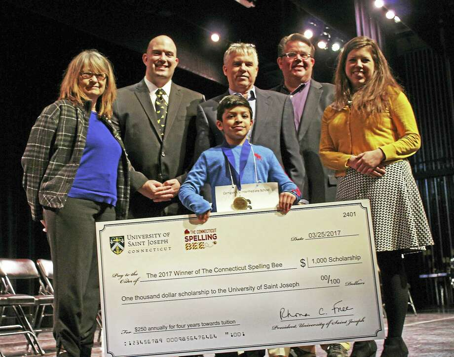 Arin Bhandari, front center, displays a $1,000 scholarship awarded to him by the University of Saint Joseph for winning The Connecticut Spelling Bee. Also pictured are, from left, Connecticut Spelling Bee judge Catherine Kurkjian, pronouncer Dr. William Dolan, judge Andrew Julien, judge Mark Zelinsky and Jennifer DiCola Matos, executive director of the Noah Webster House & West Harford Historical Society. Photo: CONTRIBUTED PHOTO — University Of Saint Joseph