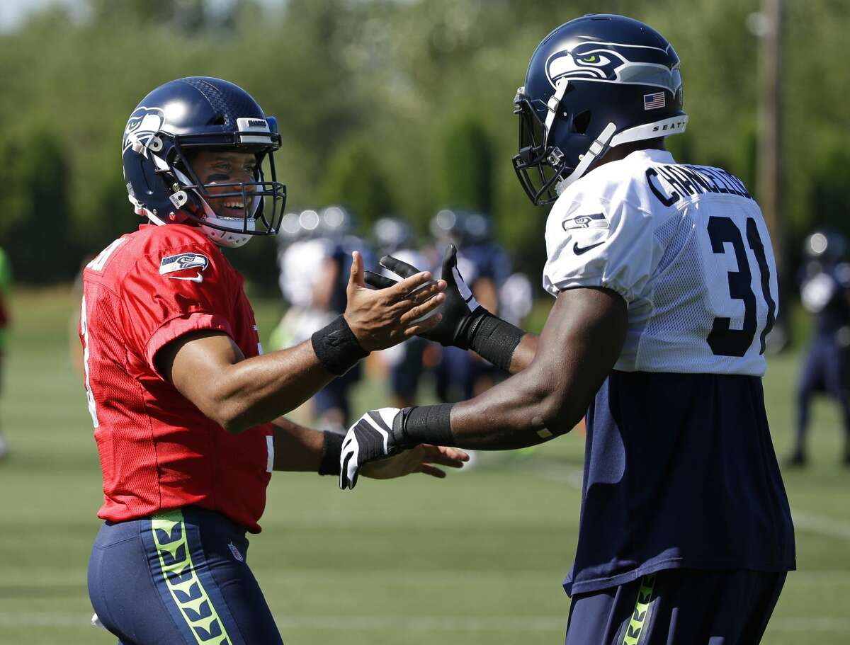 Seattle Seahawks quarterback Russell Wilson, left, greets strong safety Kam Chancellor at the start of NFL football training camp, Tuesday, Aug. 1, 2017, in Renton, Wash. (AP Photo/Ted S. Warren)