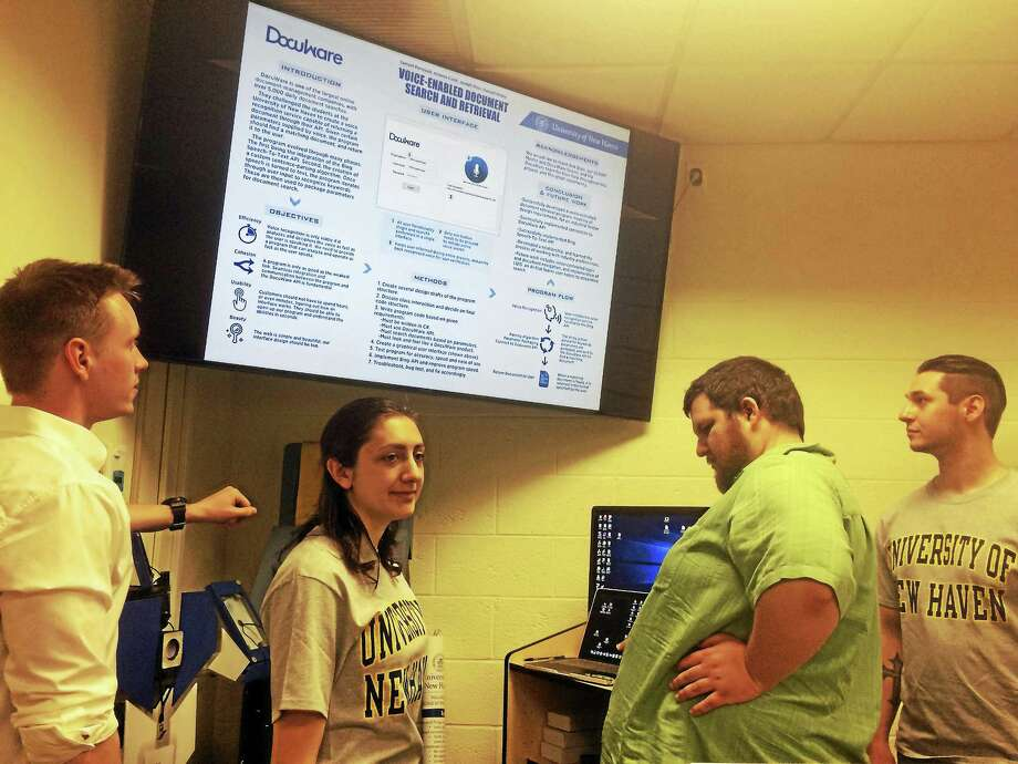 University of New Haven computer science students Samuel Perreault of Providence, R.I., Arianna Conti of Brewster, N.Y., Donald Sbabo of North Haven and Joseph Ricci of North Haven talk about the new voice recognition filing software program they created for DocuWare, a Wallingford-based document management company, as part of a senior project for Assistant Professor Frank Breitinger's Senior Design class. Photo: Mark Zaretsky — New Haven Register