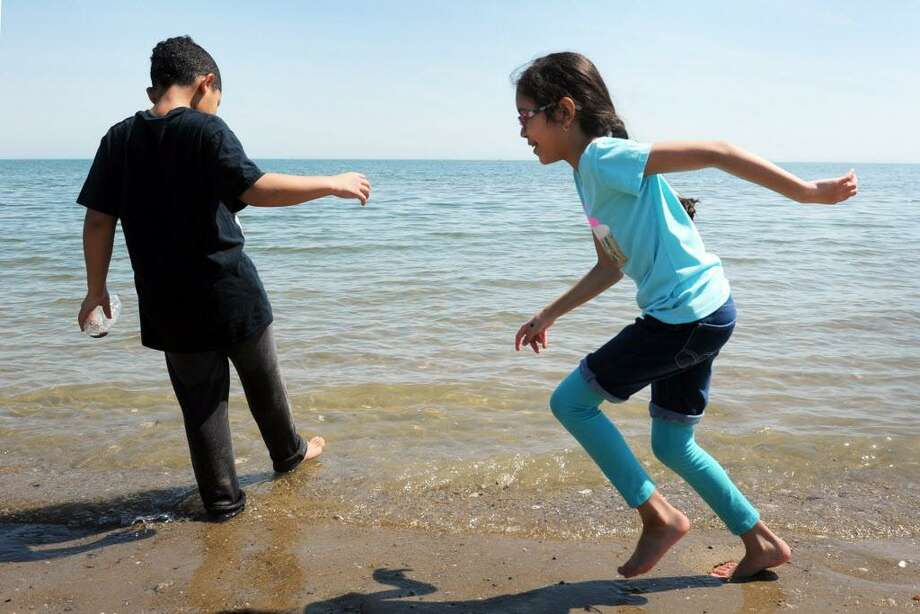 Raymond Morales and Karylane Velazquez test the waters of Long Island Sound on their first trip of the season to the beach at Seaside Park, in Bridgeport, Conn. April 11, 2017. Photo: Ned Gerard / Hearst Connecticut Media / Connecticut Post